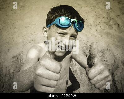 Boy's hands on the beach showing thumbs up - Stock Image