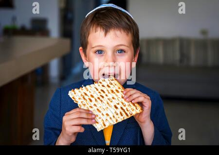 Cute Caucasian child in a yarmulke taking a bite from a traditional Jewish matzo unleavened bread in a room. - Stock Image