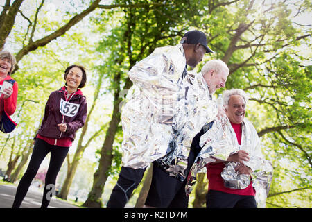 Active senior men finishing sports race, wrapped in thermal blankets - Stock Image