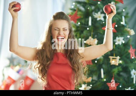 happy modern woman in red dress near Christmas tree rejoicing - Stock Image