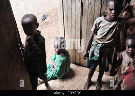 A young Ugandan child who is HIV positive sits on the doorstep of his house, staring at the camera with his siblings - Stock Image