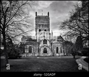 A moody & atmospheric monochrome image of Tewkesbury Abbey. This fantastic English Parish Church has a famous Romanesque Crossing Tower and hosts the annual Musica Deo Sacra. Photo © COLIN HOSKINS. - Stock Image