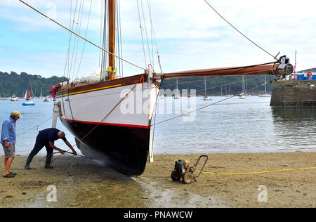 Power washing the hull of a Falmouth Working Boat on the beach at St Mawes, Roseland Peninsula, Cornwall, South West England, UK - Stock Image