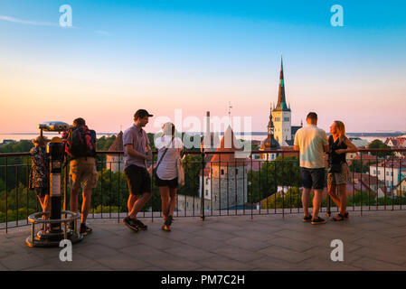 Baltic light city, view of tourists gathered on a terrace on Toompea Hill in Tallinn to watch the sunset over the medieval Old Town quarter, Estonia. - Stock Image