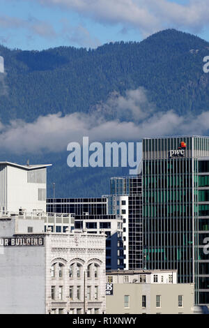 Close-up of old and new downtown buildings with North Shore Mountains in background, Vancouver, BC, Canada - Stock Image