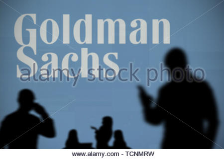 The Goldman Sachs logo is seen on an LED screen in the background while a silhouetted person uses a smartphone in the foreground (Editorial use only) - Stock Image