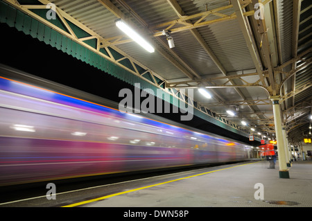 British railway station platform at night with a train passing through as a colourful streak of light - Stock Image