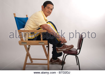 Elderly man laces his walking shoes. - Stock Image