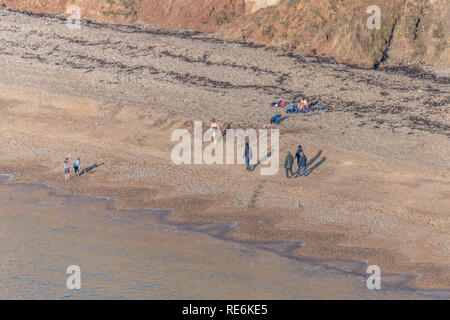 Wareham, UK. Sunday 20th January 2019. Visitors enjoy the winter sun at Worbarrow Beach on the Jurassic Coast in Dorset. People are wrapped up warm in the 4 degree cold but sunny weather. Credit: Thomas Faull/Alamy Live News - Stock Image