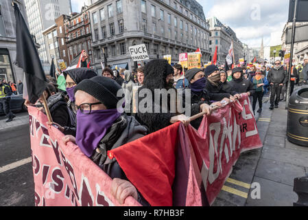 London, UK. 9th Dec, 2018. Anti-fascists march behind a banner 'The Enemy doesn't arrive by boat - He arrives by Limousine. No to Fortress Britain', The united counter demonstration by anti-fascists marches in opposition to Tommy Robinson's fascist pro-Brexit march. The march which included both remain and leave supporting anti-fascists gathered at the BBC to to to a rally at Downing St. Police had issued conditions on both events designed to keep the two groups well apart. Credit: Peter Marshall/Alamy Live News - Stock Image