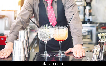 Young bartender making cocktails at bar counter - Barman serving drinks - Work, passion and mixologist concept - Stock Image