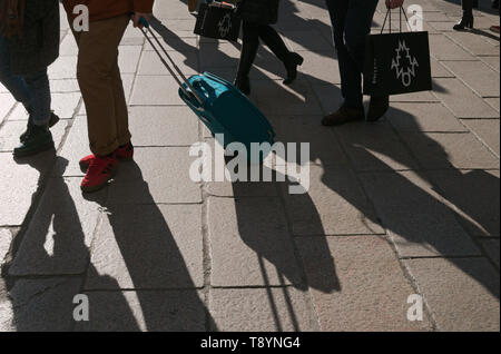 unrecognizable shoppers and pavement with shadows, Milan, Italy - Stock Image