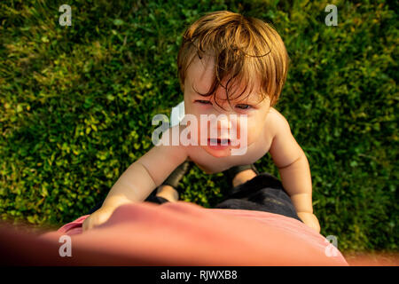 A baby girl looks up at the camera while crying. - Stock Image