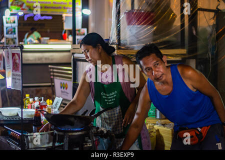 BANGKOK, THAILAND - NOVEMBER 2018: Thai muslim couple are preparing and cooking thai food in the evening on the night market - Stock Image