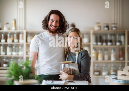 A portrait of two shop assistants standing in zero waste shop, looking at camera. - Stock Image