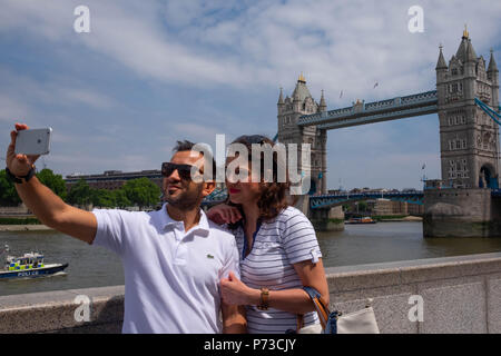 London, England. 4th July 2018. Georgia and her boyfriend, tourists from Greece, take a selfie near Tower Bridge on another very hot day. The present heatwave is set to continue. ©Tim Ring/Alamy Live News - Stock Image