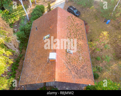 Inspection of the red tiled roof of a single-family house, inspection of the condition of the tiles on the roof of a detached house. - Stock Image