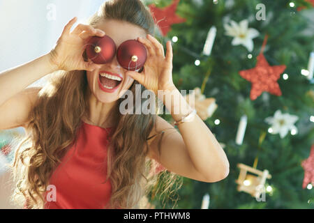 happy stylish woman in red dress near Christmas tree having fun time - Stock Image