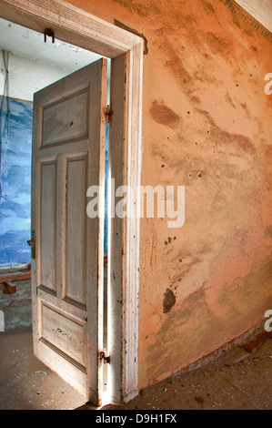 Open door to a room full of sand in Kolmanskop, a ghost mining town in Namibia, Africa. The desert has reclaimed - Stock Image