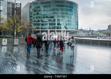 A group of tourists walking around the More London development area on the South Bank in London. - Stock Image