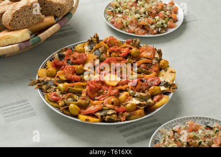 Traditional  Moroccan dish with sardines and vegetables, salad and a basket with bread - Stock Image