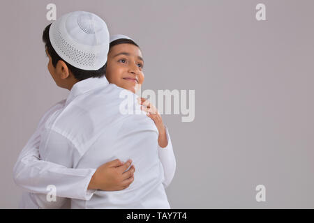 Young Muslim boys with caps hugging each other - Stock Image