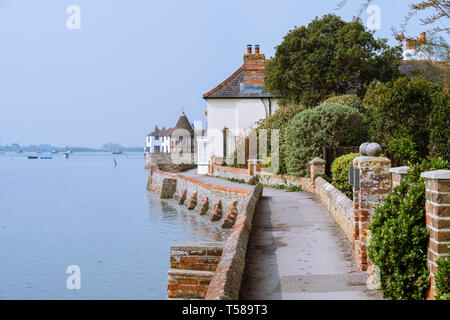 Shore Path walkway village on Bosham Creek at high tide in Chichester harbour. Bosham, West Sussex, England, UK, Britain - Stock Image