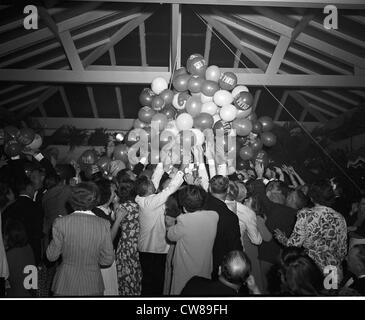 A crowd reaches for balloons suspended from rafters during Gala Night at The Patio, an exclusive club in Palm Beach, - Stock Image