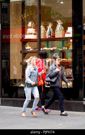 A young woman wearing a red jacket stops to look at the fancy hand-crafted cakes on display inside the Belgium Pattiserrie Valerie café in Dundee, UK - Stock Image