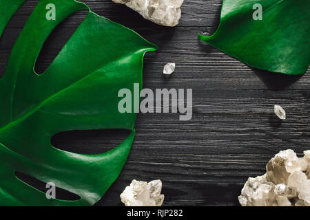 Smoky Quartz and Monstera on Black Wood with Space for Copy - Stock Image