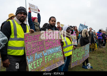 Milton Ernest, Bedford, UK. 1st December 2018. Yarls Wood Immigration Removal Centre 'Suround Yarls Wood - Shut Down Yarls Wood and all Detention Centres' demonstration. Hundreds braved the poor weather to join the protest at the remotely situated Yarls Wood IRC. Incarcerated women waved desperately at windows and their mobile phone conversations were relayed via the PA system outside the security fence. Speakers included those who had previously been imprisoned in Yarls Wood. This was the 15th Yarls Wood demonstration organised by Movement for Justice. Credit: Steve Bell/Alamy Live News - Stock Image