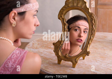 Sensual young woman in 1920s flapper dress and headband looking in an antique mirror - Stock Image