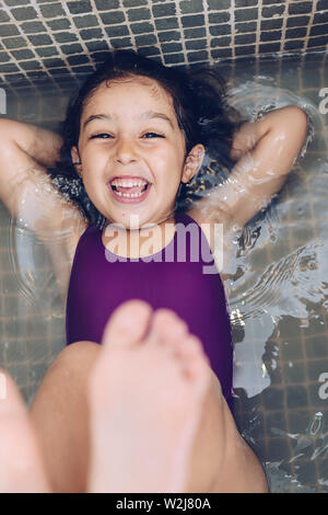 vertical photo of a playful beautiful little girl having fun and laughing lying in the tub and showing the feet while taking a bath in the bathtub, ki - Stock Image