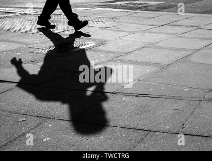 Pavement Shadow of a Person Using a Cell Phone. abstract. - Stock Image