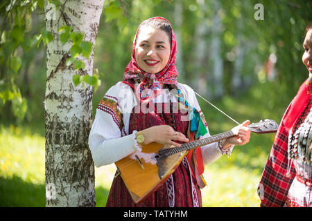 Young woman in traditional russian clothes standing in the forest and holding balalaika, midle shot - Stock Image
