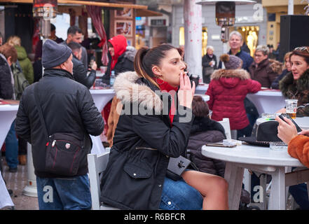 Young lady smoking sitting at table at the annual Christmas Market in Zagreb. Croatia has some of highest smoking rates in Europe - Stock Image