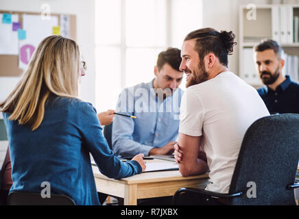 Group of young, cheerful businesspeople sitting around table in a modern office, having meeting. - Stock Image