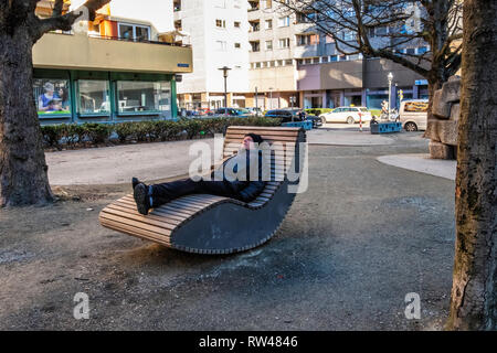Berlin,Kreuzberg. Senior elderly man relaxing on curved wooden chair on Kastanienplatz - Stock Image