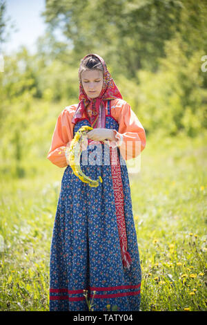 RUSSIA, Nikolskoe village, Republic of Tatarstan 25-05-2019: A young woman in traditional russian clothes making a wreath. Mid shot - Stock Image