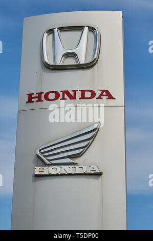 Totem poles identifying Japanese car manufacturers outside a car show room, set against a blue sky. - Stock Image