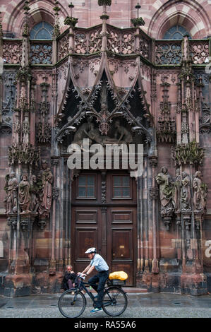 A cyclist passing the Cathedrale Notre-Dame at Strasbourg, Alsace, France - Stock Image