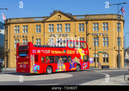The City Sightseeing Oxford open-topped tour bus passes the The Royal Oxford Hotel - Stock Image
