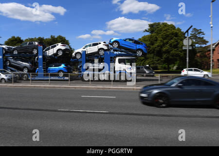 A car transporter drives along a dual carriageway fully laden with Nissan cars on way to Southampton docks for export. - Stock Image