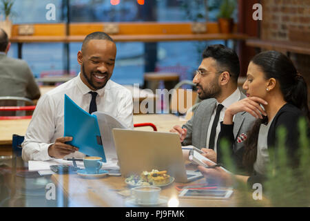 Business people discussing paperwork, working in cafe - Stock Image