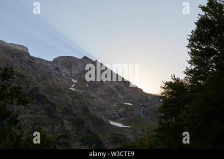 Dusk with sunbeams and Cinca waterfall in Pineta valley in Ordesa y Monte Perdido National Park (Sobrarbe, Huesca, Pyrenees, Aragon, Spain) - Stock Image