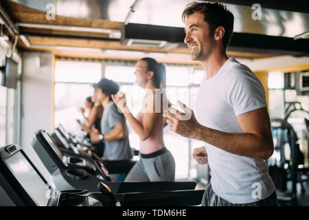 Group of young people running on treadmills in modern sport gym - Stock Image