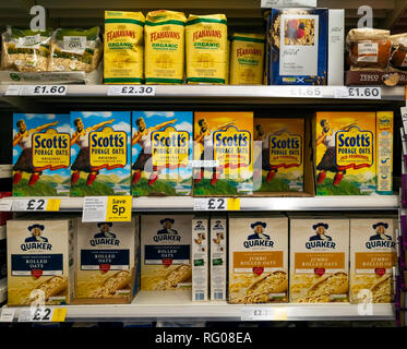Supermarket display of packages of several brands of oatmeal for making porridge the popular breakfast dish - Stock Image
