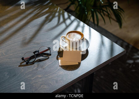 Close up of white coffee cup, glasses and business cards on dark wooden table with tropic plant on background. - Stock Image