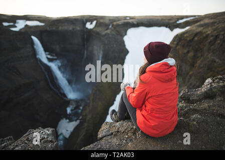 Hiker sitting on cliff by Haifoss waterfall in Iceland - Stock Image