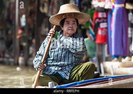 Damnoen Saduak - August 29, 2018: Elderly woman paddling her boat in Damnoen Saduak Floating Market, Ratchaburi, Thailand. - Stock Image